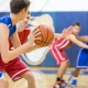 A high school basketball player holds the ball carefully outside the key as he's guarded. He's trying to decide who to pass to... (A high school basketball player holds the ball carefully outside the key as he's guarded. He's trying to decide who to p